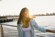 Mid adult woman laughing on city waterfront at sunset - ISF15949