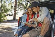 Young couple sitting on car boot pointing at map, Los Angeles, California, USA - ISF15991