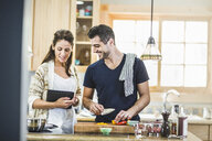 Couple preparing food and using digital tablet in kitchen - ISF16111