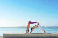 Young man and woman practicing yoga on Pacific beach, San Diego, California, USA - ISF16147