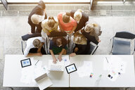 Overhead view of huddled business team meeting at desk in office - ISF16165