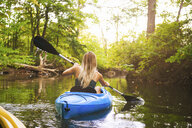 Rear view of young woman kayaking on forest river, Cary, North Carolina, USA - ISF16219