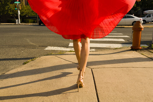 Waist down shot of young woman strolling along sidewalk wearing flowing red skirt - ISF16249