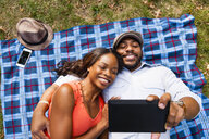 Couple lying on grass watching movie on tablet - ISF16258