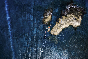 Greece, Crete, Bungee Jumping, woman jumping bungee over sea - BEF00177