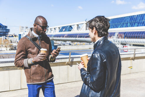 Russia, Moscow, two businessmen with coffee to go and smartphone in the city - WPEF00606