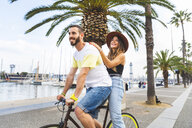 Spain, Barcelona, couple having fun and sharing a ride on a bike together on seaside promenade - WPEF00620