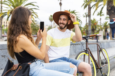 Spain, Barcelona, happy couple sitting on bench taking a smartphone picture - WPEF00623
