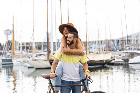 Spain, Barcelona, happy couple with bicycle at the seaside - WPEF00626