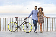 Spain, Barcelona, couple with bicycle standing at the seaside - WPEF00629