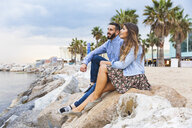 Spain, Barcelona, couple sitting on rocks at the seaside - WPEF00632