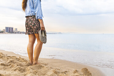 Spain, Barcelona, woman standing barefoot on the beach - WPEF00638