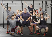 Portrait of eight people flexing muscles in gym - ISF16304