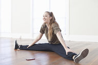 Teenage girl warming up and doing the splits in ballet school - ISF16351
