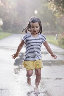 Barefoot girl running through puddles on rainy street - ISF16394