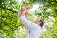 Grandfather lifting up baby granddaughter in park - ISF16406