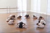 Children sitting on floor practicing ballet with teacher in ballet school - ISF16409