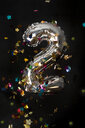 Silver balloon and confetti for second birthday in front of black background - AWDF00744