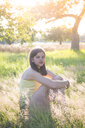Young girl sitting on meadow at summer evening - LVF07215