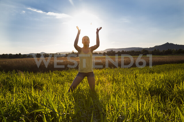 Young girl standing on meadow at summer evening, against the sun, holding sun - LVF07221