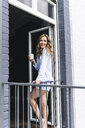 Smiling woman in pyjama at home with cup of coffee looking out of balcony door - UUF14326