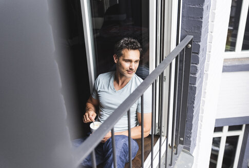 Man in pyjama at home with cup of coffee looking out of balcony door - UUF14329