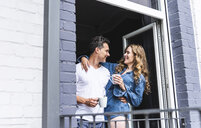 Smiling couple in nightwear at home with cups of coffee at balcony door - UUF14335