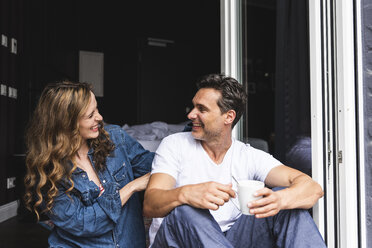 Happy couple in nightwear at home sitting at French window - UUF14344