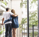 Rear view of couple in nightwear standing on balcony hugging - UUF14365