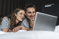 Happy couple lying on bed at home looking at laptop - UUF14371