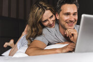 Happy couple lying on bed at home looking at laptop - UUF14374