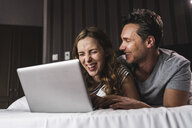 Happy couple lying on bed at home having fun with laptop - UUF14377