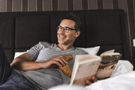 Happy man lying in bed at home with croissant and book - UUF14383