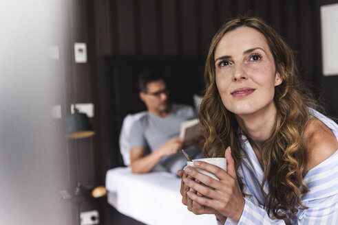 Smiling woman with cup of coffee in bedroom with man in background - UUF14386