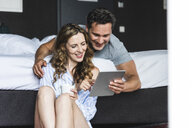 Happy couple in bedroom at home looking at tablet - UUF14389