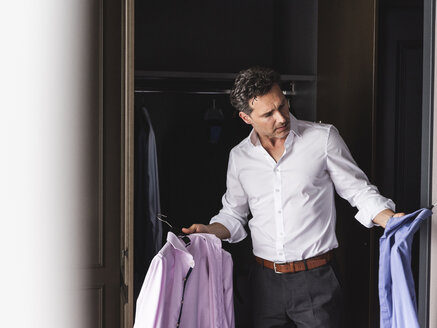 Businessman at home getting dressed choosing shirt from wardrobe - UUF14395