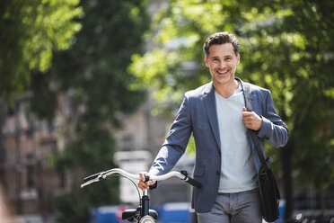 Portrait of smiling man pushing bike in the city - UUF14416