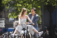 Happy carefree couple with bicycle in the city - UUF14425