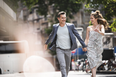 Happy carefree couple running in the city - UUF14428