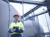 Portrait of worker holding digital tablet at biomass facility - CUF38923