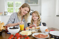 Mother and daughter eating at kitchen table - CUF39036