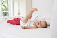 Baby girl lying on bed with legs raised - CUF39066