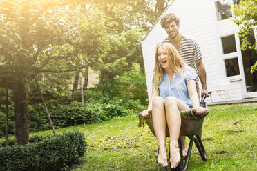 Young couple playing with wheel barrow in garden - CUF39114