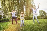 Female members of family playing with hula hoop - CUF39126