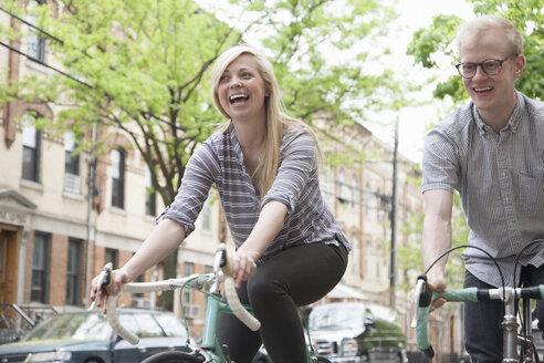 Young couple laughing whilst cycling along street - ISF16483