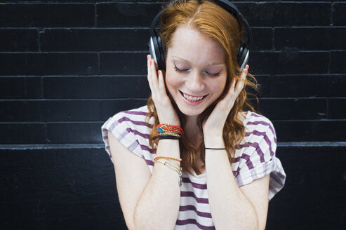 Portrait of young woman wearing headphones - ISF16519
