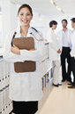 Smiling doctor holding clipboard - CUF39214