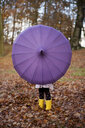 Girl playing with umbrella in park - CUF39253