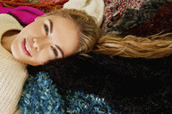 Portrait of young woman lying on furry blanket - CUF39451
