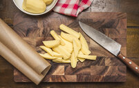 Still life of peeled and sliced potatoes, kitchen knife on chopping board - CUF39523